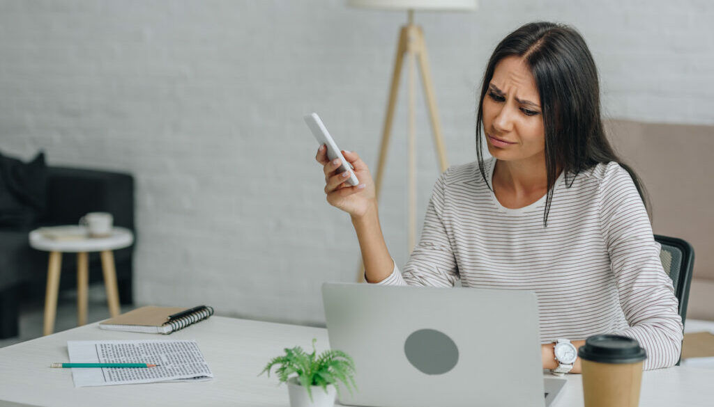 woman looking at laptop screen in frustration